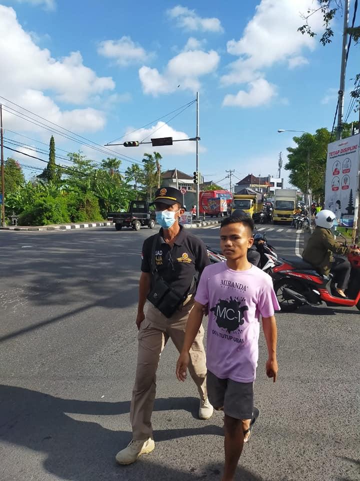 PETUGAS Satpol PP Denpasar menggiring salah seorang pelanggar prokes yang terjaring saat operasi yustisi, Jumat (2/7/2021). Foto: ist