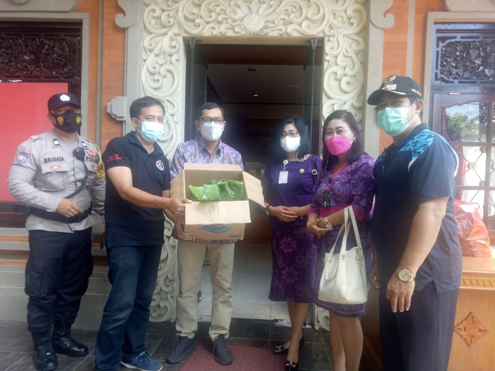 Plt. Kadisdikpora Kota Denpasar, IGN Eddy Mulya, Jumat (30/7/2021) menyerahkan 250 bungkus nasi jinggo kepada masyarakat Desa Sumerta Kauh. Foto: tra