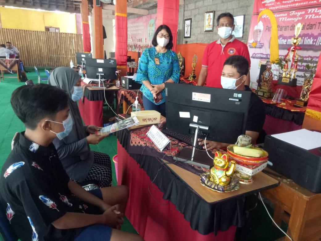 KEPALA SMA PGRI 2 Denpasar, I Komang Arta Saputra; bersama Wakasek Humas AA Ayu Seriati memantau pendaftaran siswa baru yang terus mengalir ke SMA PGRI 2 Denpasar. Foto: tra