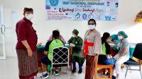 KABID SMP Disdikpora Kota Denpasar, AA Gede Wiratama; bersama Kasek Ni Putu Supadmi, memantau vaksinasi Covid-19 untuk anak usia 12-17 tahun di SMP Nasional Denpasar. Foto: ist