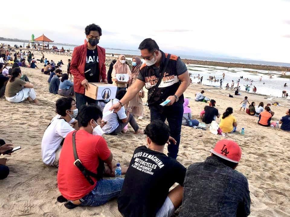 WANDHIRA saat membagikan masker bersama para mahasiswa dari Ikatan Mahasiswa Muhammadiyah di Pantai Sanur, beberapa waktu lalu. Foto: ist