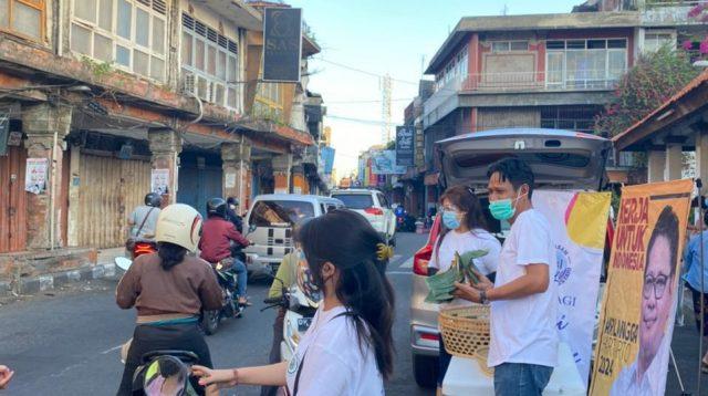 """RELAWAN Demer dalam Yayasan GSL membagikan """"nasi jinggo Airlangga"""" kepada pedagang pasar dan warga yang melintas di depan Pasar Badung, Denpasar, Jumat (23/7/2021). Kegiatan ini digelar selama 10 hari di Buleleng dan Denpasar. Foto: Ist"""