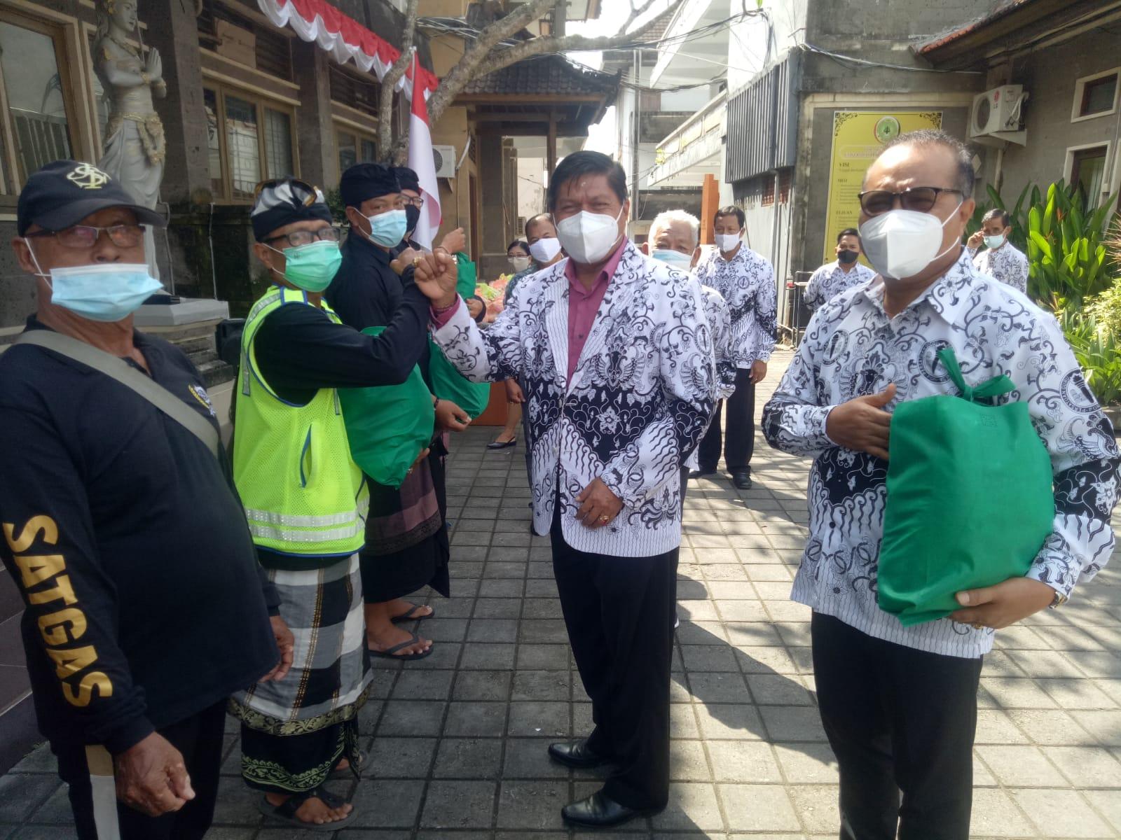 KETUA PGRI Kota Denpasar, I Ketut Suarya, bersama Rektor Universitas PGRI Mahadewa Indonesia, I Made Suarta, menyerahkan sembako kepada Satgas Covid-19 Kelurahan Tonja, Senin (9/8/2021). Foto: tra