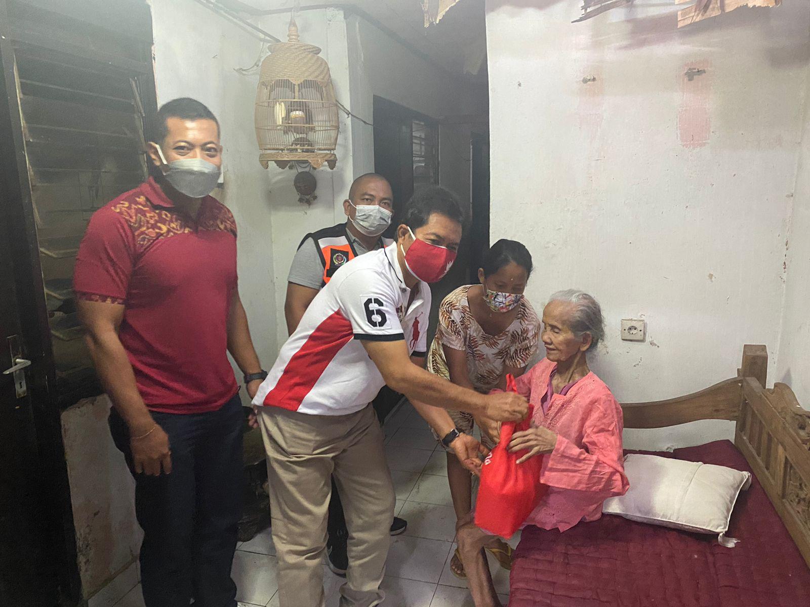 KADIS Koperasi UMKM Kota Denpasar, I Made Erwin Suryadarma; bersama Ketua Karang Taruna Kota Denpasar, I Ketut Ngurah Aryawan, menyerahkan bantuan sembako kepada penyandang disabilitas, Minggu (22/8/2021). Foto: ist