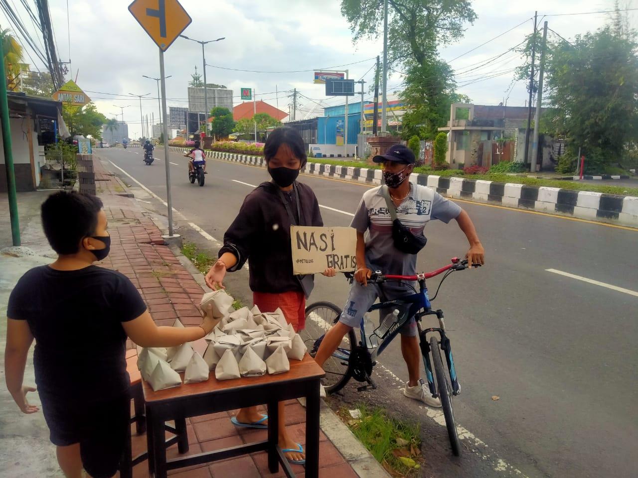 AKSI bagi nasi bungkus gratis kepada pengguna jalan di Nusa Dua, Kuta Selatan, Badung, Selasa (3/8/2021). Foto: ist