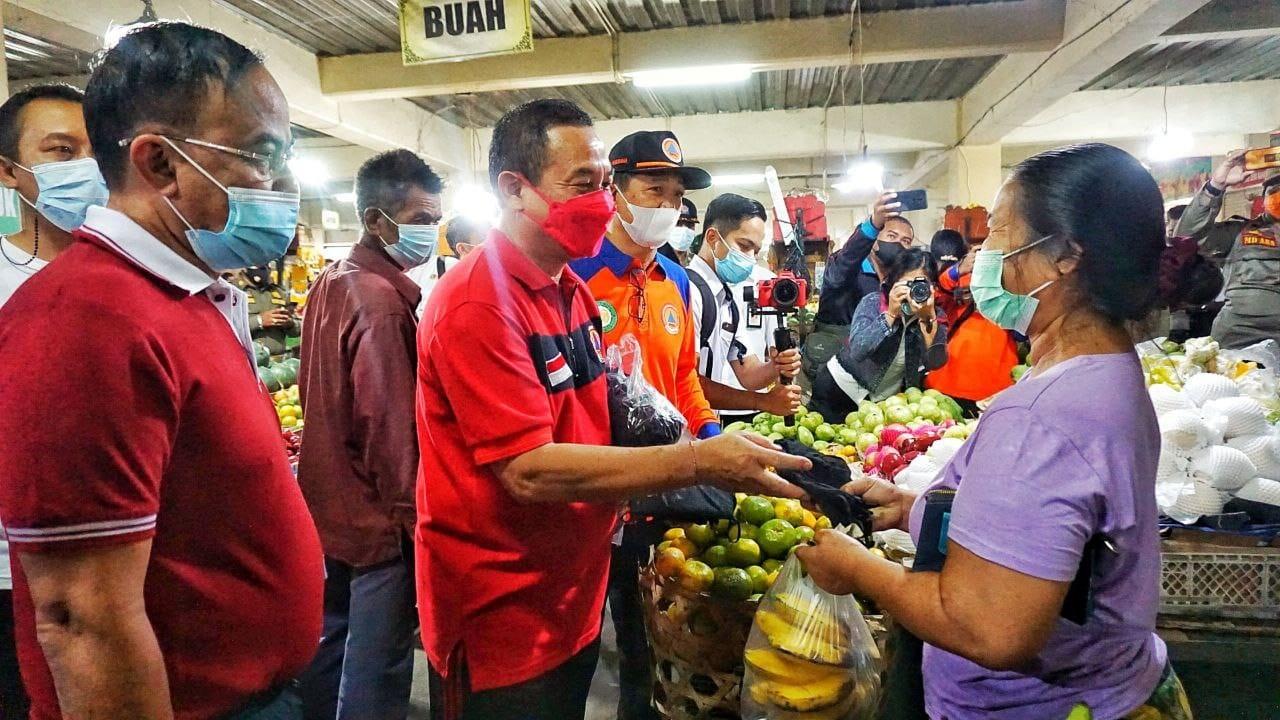 BUPATI Karangasem, I Gede Dana, saat membagikan masker kepada pedagang di pasar. Pemkab Karangasem berencana menambah anggaran di APBD Perubahan tahun 2021 untuk penanganan isolasi terpusat (isoter). Foto: ist