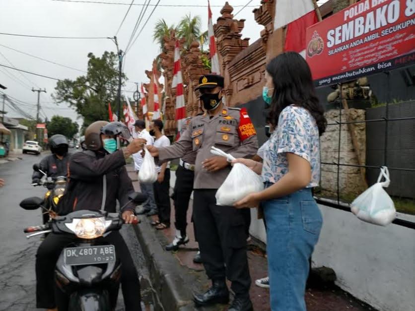 BULAN Sutena mendampingi Kapolsek Ubud membagikan sembako gratis. Foto: adi