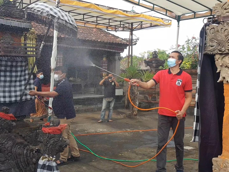ANGGOTA DPRD Bali, AA Wira Mantara; dan anggota DPRD Gianyar, Wayan Gede Pradnyana, menyemprotkan eco enzyme di Pura Besi Desa Lebih, Gianyar. Foto: adi