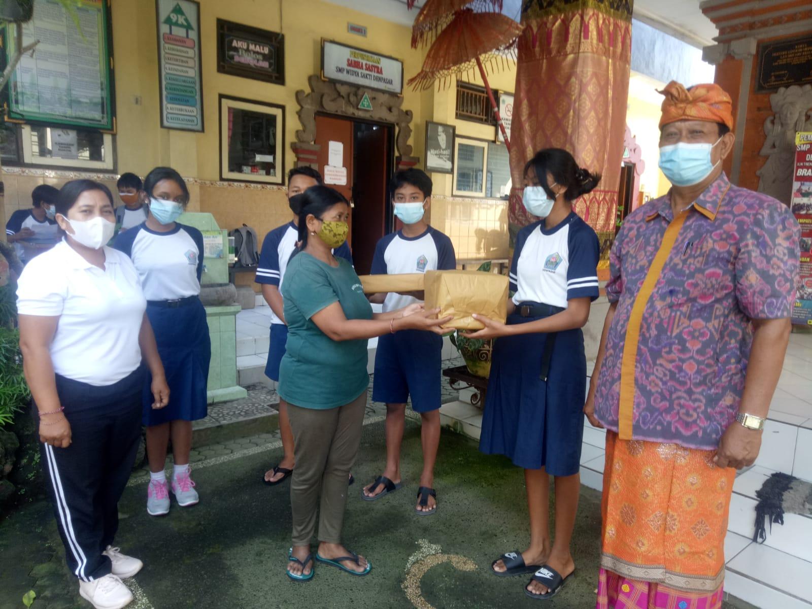 OSIS SMP Widya Sakti Denpasar didampingi Kasek Wayan Nendra menyerahkan bingkisan sembako pada warga Kelurahan Penatih yang terdampak pandemi Covid-19. Foto: tra