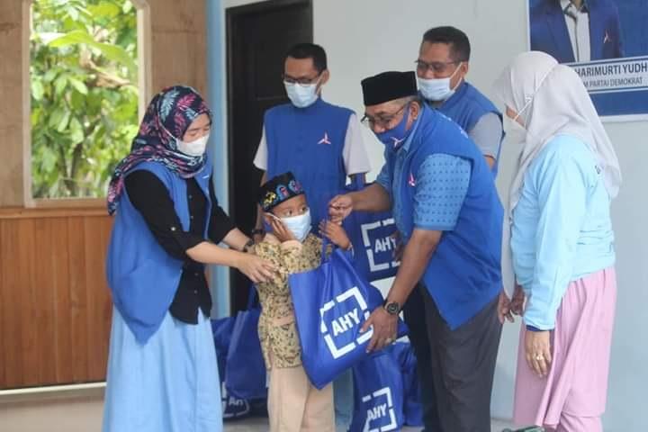KETUA DPD Partai Demokrat NTB, TGH Mahally Fikri, didampingi istri dan para kader Demokrat membagikan paket sembako kepada anak yatim dan masyarakat kurang mampu di Lombok Barat, Jumat (20/8/2021). Foto: rul