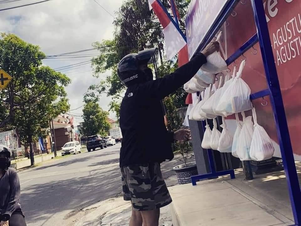 WARGA mengambil bungkusan berisi sembako, susu, gula, dan masker yang digantung di stan Nasdem Peduli di DPW Partai Nasdem Bali, Jalan Tukad Batanghari Nomor 7, Denpasar. Foto: ist
