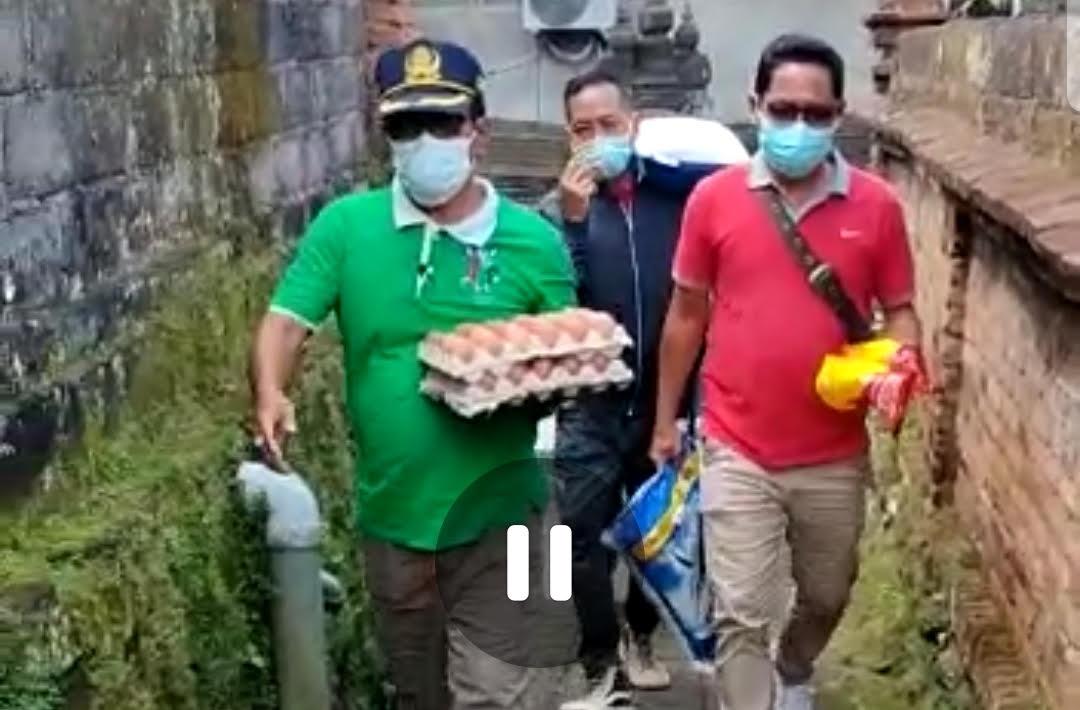 PERBEKEL Desa Siangan, I Ketut Berata, didampingi aparat desa membawa bantuan untuk warga yang menjalani isoman. Foto: adi