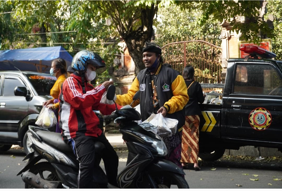 RELAWAN Yayasan Gumi Suci Lestari (GSL) yang dikelola I Gede Sumarjaya Linggih bergerak membagikan nasi bungkus ke warga yang melintas di Jalan Gajah Mada, Banjar Kodok, Kelurahan Karangasem, Selasa (10/8/2021). Foto: ist