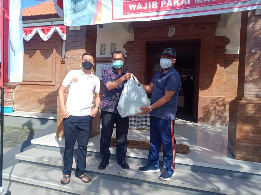 KEPALA SMP Dharma Praja Denpasar, I Nyoman Duma Asmaranata, saat menyalurkan 200 bungkus nasi jinggo yang diterima Perbekel Desa Dauh Puri Kaja, I Gusti Ketut Sucipta, Jumat (6/8/2021). Foto: ist