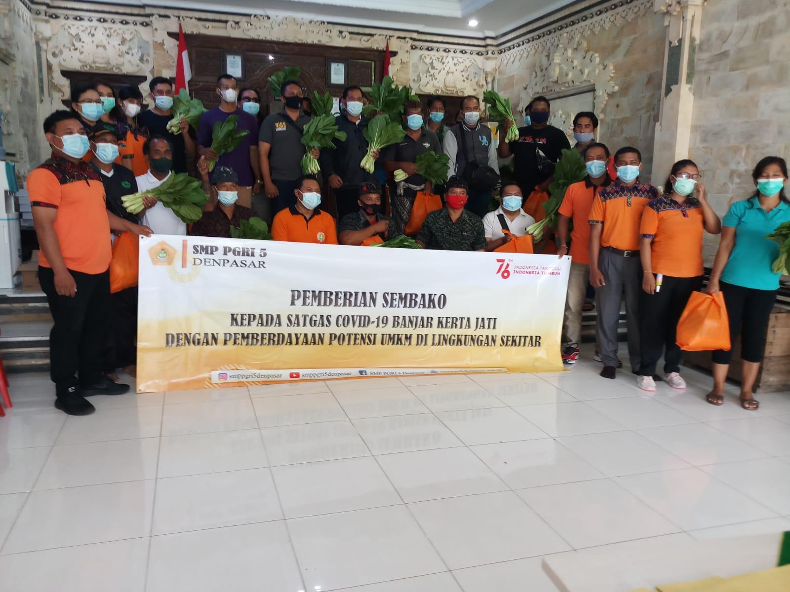 Plt. Kepala SMP PGRI 5 Denpasar, Made Raditya Berata, bersama staf saat membagikan paket sembako dan sayur pada Satgas Covid-19 dan warga di lingkungan Banjar Kertajati, Desa Pemecutan Kaja, Denpasar Utara, Senin (16/8/2021). Foto: ist