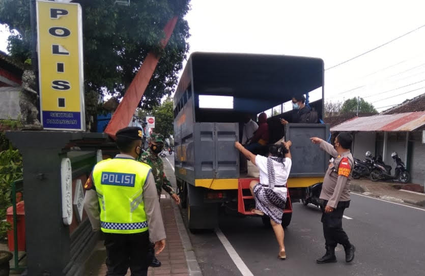 PERSONEL Polsek Payangan menjemput warga yang menjadi pasien terkonfirmasi positif Covid-19 untuk menjalani isolasi terpusat (isoter) di Hotel Evitel Ubud, menggunakan truk Dalmas, Jumat (20/8/2021). Foto: adi