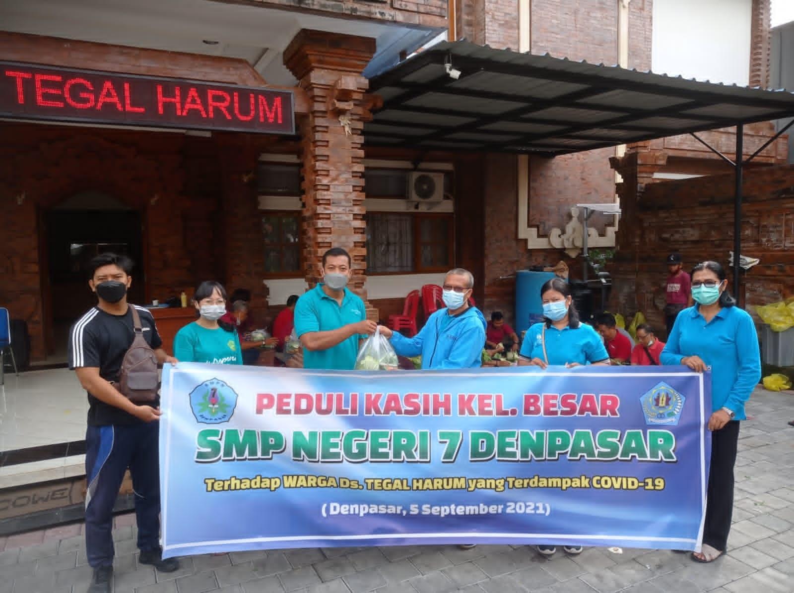 WAKASEK Kurikulum SMPN 7 Denpasar, Made Asmara, bersama staf, menyerahkan bantuan paket sayur mayur yang diterima Perbekel Desa Tegal Harum, I Komang Adi Widiantara. Foto: tra