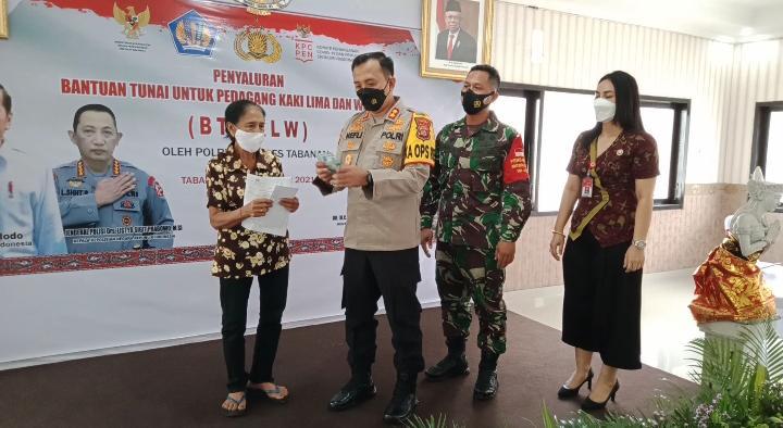 KAPOLRES Tabanan, AKBP Ranefli Dian Candra, ketika menyalurkan bantuan tunai langsung kepada para pedagang kakilima dan warung, di Aula Wisnu Hartono Polres Tabanan, Sabtu (18/9/2021). Foto: ist