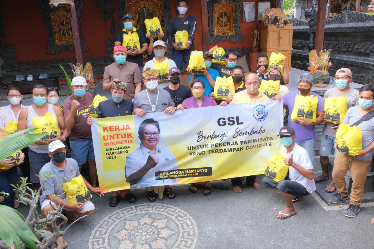 SUMARJAYA Linggih bersama para kader Partai Golkar saat membagikan bantuan paket sembako kepada keluarga pekerja pariwisata di Badung, Senin (13/9/2021). Foto: ist
