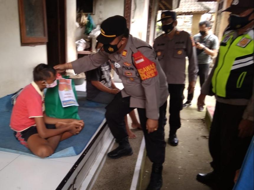 KAPOLSEK Payangan, AKP I Putu Agus Ady Wijaya, menyerahkan bantuan sembako kepada penyandang difabel di Dusun Karang Suwung, Sabtu (4/9/2021). Foto: ist