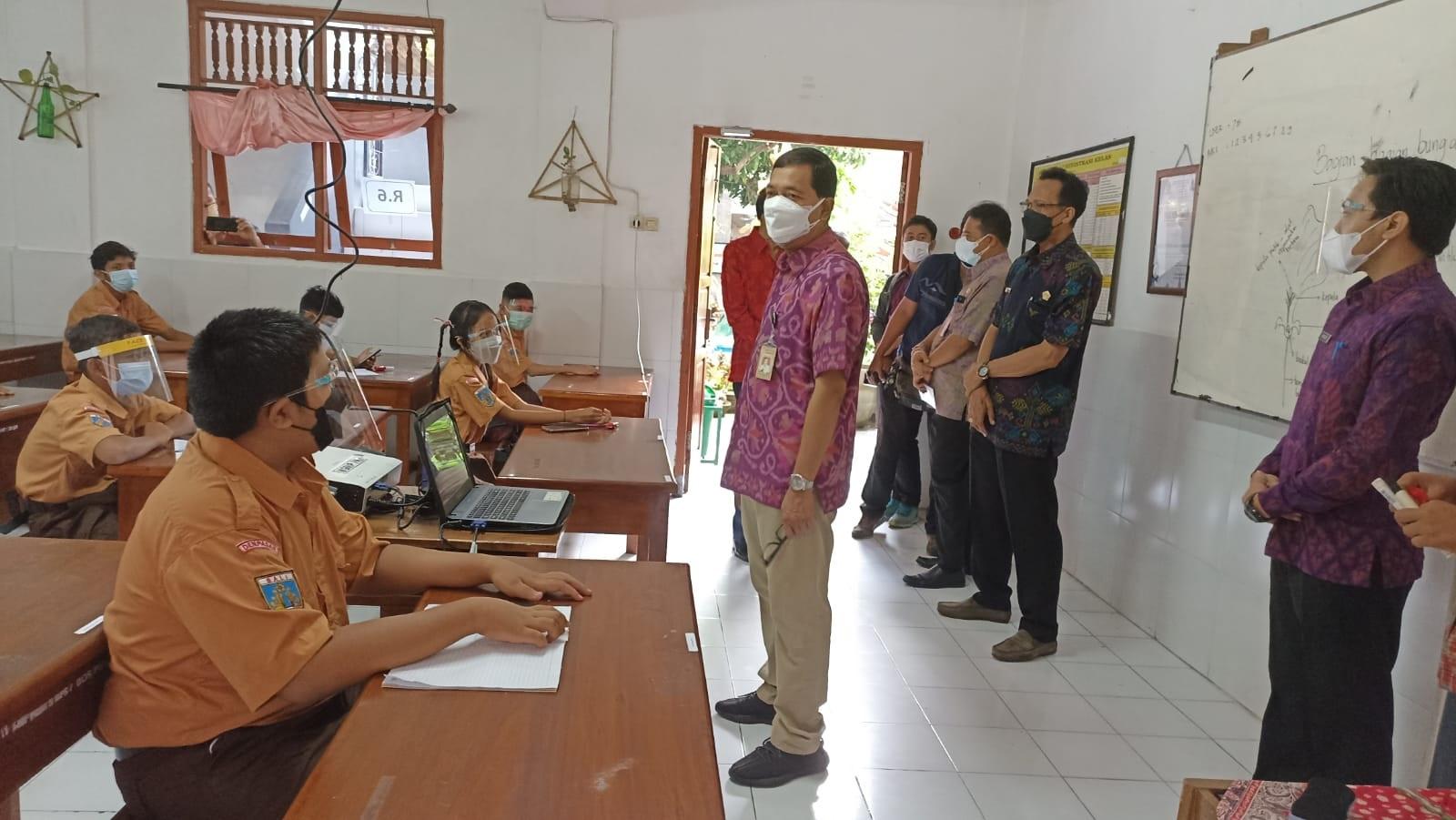 PLT Kepala Dinas Pendidikan Kepemudaan Olahraga Kota Denpasar, IGN Eddy Mulya, saat memantau pelaksanaan PTM Terbatas di SMP PGRI 3 Denpasar. Foto: tra